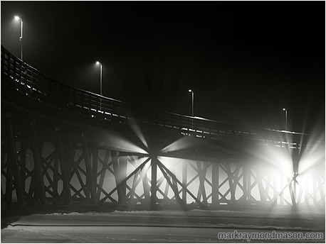 Fine art black and white photo showing light streaming through the crossed beams of an ice-locked wharf in the night