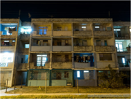 Fine art photograph showing lights in the windows of a very old and run-down apartment complex