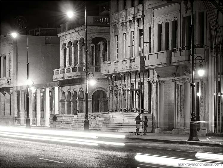 Buildings, Streaked Lights, Figures: Havana, Cuba (2017-02-13) - Fine art black and white photograph showing 2 figures beneath colonial architecture, through white streaked headlights