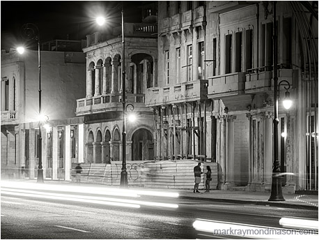 Fine art black and white photograph showing 2 figures beneath colonial architecture, through white streaked headlights