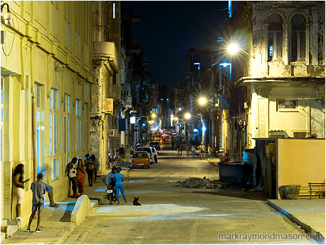 Fine art photograph showing a night time street scene in downtown Havana lit by garish street lamps