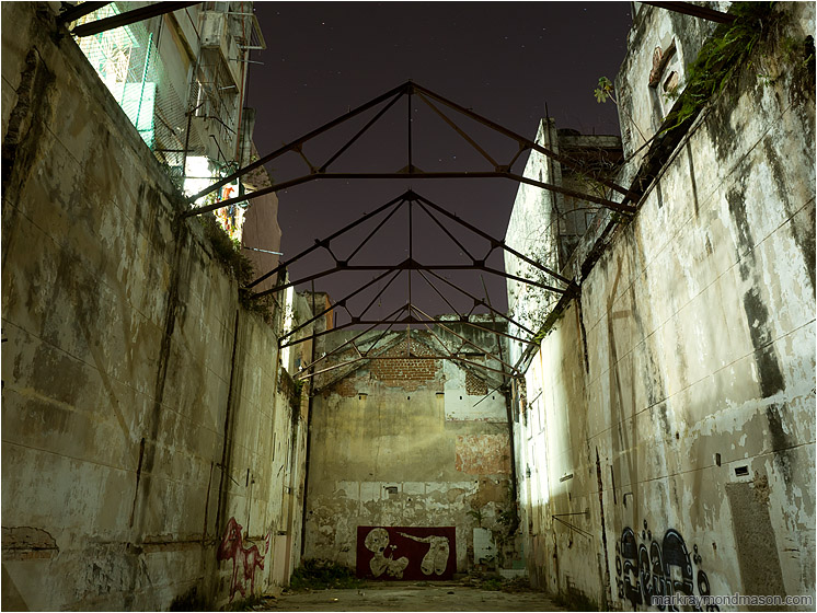 Graffiti, Steel Trusses, Night Sky: Havana, Cuba (2017-02-14) - Fine art photograph showing a vacant urban canyon between concrete buildings, with exposed trusses against a starry sky