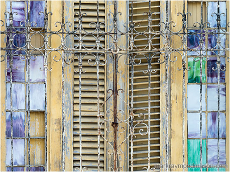 Abstract photography showing small stained glass windows and wooden shutters behind ancient wrought-iron bars