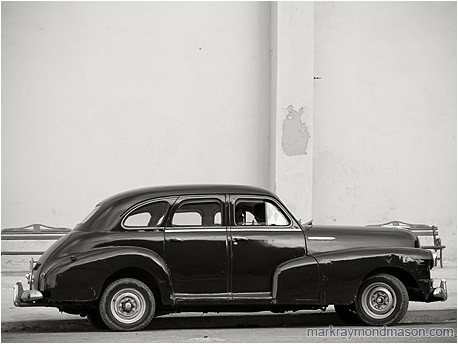 Fine art black and white photograph showing silhouetted lovers in a battered 1950s model car, parked beside a plain concrete wall
