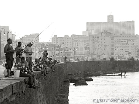 Black and white landscape photograph showing men fishing from the Malecon, with the ancient buildings of Havana in the background