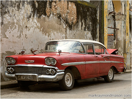 Fine art photograph of a dingy 1950s era car in soft light, in front of a checked and stained concrete wall