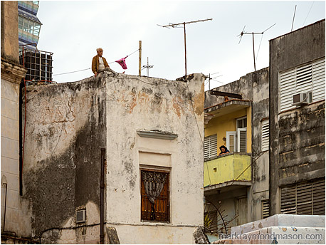 Fine art photograph showing a man perched unsettlingly on top of a concrete building and a woman looking into the street from a mid-level apartment