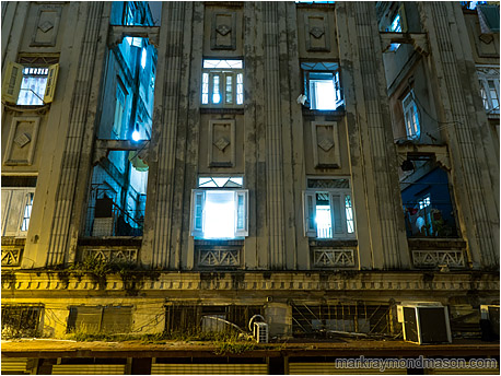 Fine art photograph showing windows open to the night and spilling blue light into the arc-sodium lit streets