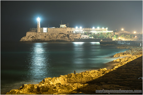 Fine art photograph of a figure on the rocks by the sea, with floodlights on a fortress and a lighthouse in the background