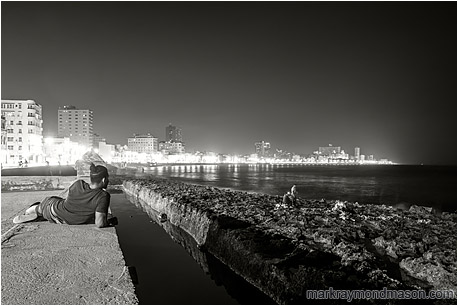 Fine art black and white photograph of a man resting on the seawall in Havana, taking in the city lights and a party fishing by lamplight