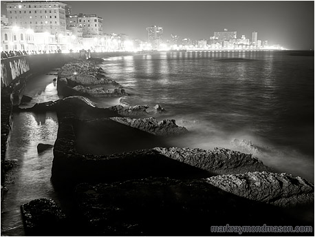 Fine art black and white night photograph of waves crashing against worn concrete water barriers