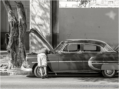 Fine art black and white photo showing a man bending into the open hood of a finely restored classic car