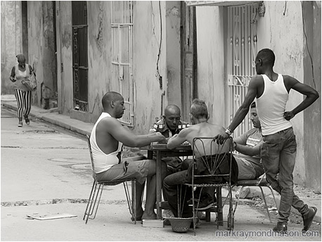 Fine art black and white photograph showing a group of men playing dominoes at a table in the street, and a woman with a cigarette and shopping bag in the background