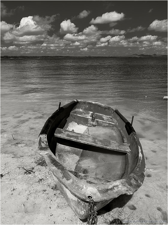 Battered Boat, Rolling Clouds: Near Vinales, Cuba (2017) - Fine art black and white photograph showing a flooded boat, cocked sideways, sitting abandoned on the silty shores of a shallow lake