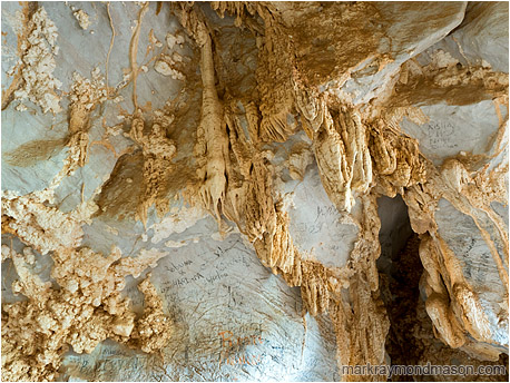 Abstract photo showing popcorn rock and stalactites on the roof of a cave, with black charcoal graffiti all around