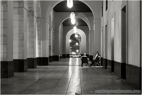 Fine art black and white photograph showing several bank guards lounging in chairs in an empty breezeway