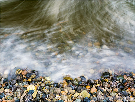 Fine art photograph showing intertwined, blurry waves moving over round multi-coloured beach rocks