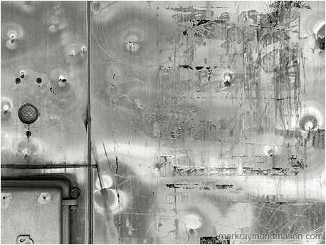 Fine art abstract black and white photo showing a closeup of a dented metal train kiosk, reflected light forming patterns in the surface